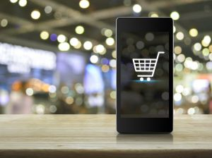 Shopping cart Icon on smart phone screen over blur mall